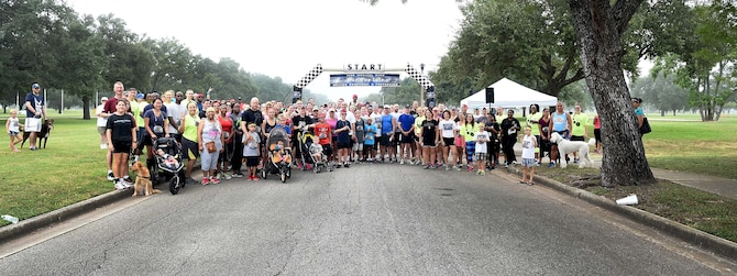 Airmen, civilians and their families participating in the 4th Annual 5K Run for Life event pose for a group photo at Heritage Park on Joint Base San Antonio-Randolph, Texas, Sept. 24, 2016. Hosted by the 59th Medical Wing, the annual event aims to raise awareness of suicide and suicide prevention. (U.S. Air Force photo/Staff Sgt. Jerilyn Quintanilla)
