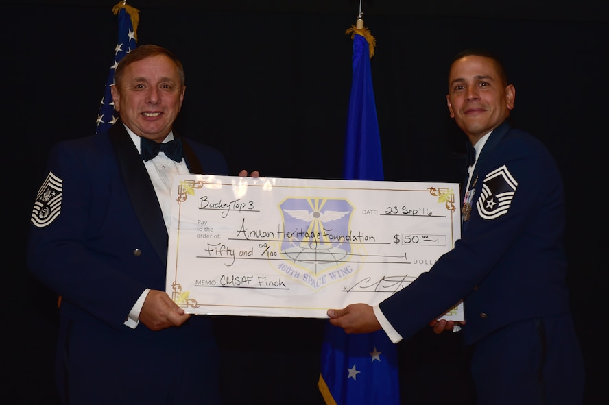 """Former Chief Master Sgt. of the Air Force Frederick J. """"Jim"""" Finch receives a check on behalf of the Airmen Heritage Foundation from Senior Master Sgt. Carlos Martinez, 2nd Space Warning Squadron director of staff, during a senior NCO induction ceremony Sept. 23, 2016, Heritage Eagle Bend Golf Course in Aurora, Colo. The Airmen Heritage Fund provides support to the U.S. Air Force Airmen Heritage Museum, Enlisted Character Development Center and other heritage-related activities in hopes of preserving and honoring the history and heritage of enlisted Airmen. (U.S. Air Force photo by Airman 1st Class Gabrielle Spradling/Released)"""