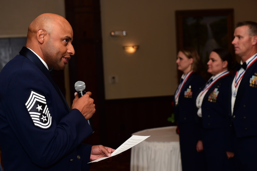 Chief Master Sgt. Rod Lindsey, 460th Space Wing command chief, reads the senior NCO charge during an induction ceremony Sept. 23, 2016 Heritage Eagle Bend Golf Course in Aurora, Colo. The charge provided an outline of what SNCO's are responsible for doing, including helping leaders make informed decisions, be an active and visible leader, and to promote responsible behaviors within all Airmen. (U.S. Air Force photo by Airman 1st Class Gabrielle Spradling/Released)