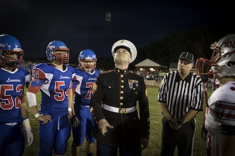 Sgt. Erik Brown, canvassing recruiter for Recruiting Substation Manchester, New Hampshire, tosses the coin at the start of the Londonderry vs. Pinkerton high school football game, Sept. 23, 2016. The game is part of the Great American Rivalry Series, a series of high school football games between schools with historic sports rivalries. During and after the game, the Marines and GARS recognized football players with the highest GPA of their teams and players that contributed most to the game and the sport as a whole.