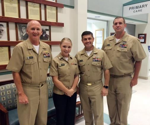 """(Left to right) Capt. David Collins, commanding officer, Naval Hospital Jacksonville, Florida, joins Naval Branch Health Clinic-Albany's team: Petty Officer 3rd Class Hailey McAdams, laboratory assistant, Lt. Cmdr. Kenneth Shaw, officer-in-charge and Chief Petty Officer Eric Jackson in a ceremony to meritoriously promote McAdams, recently. The meritorious achievement, which was held at NBHC-Albany, chronicled a """"first"""" in the Albany clinic's history."""