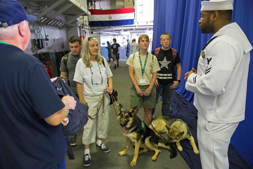 Navy Petty Officer 2nd Class Erik Bryant provides information as a tour guide for members of the Seeing Eye Puppy Training Program.