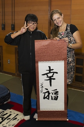 Julita Bryant, a Marine Corps Air Station Iwakuni resident, poses for a photo with calligraphy she painted at the Kumano Brush Festival in Kumano, Japan, Sept. 22, 2016. Air station residents traveled to Kumano with the Cultural Adaptation Program and were able to participate in a calligraphy competition with the Japanese locals. After attending the festival the residents visited the Fudenosato Kobo Museum where they learned how calligraphy equipment is made. (U.S. Marine Corps photo by Lance Cpl. Joseph Abrego)