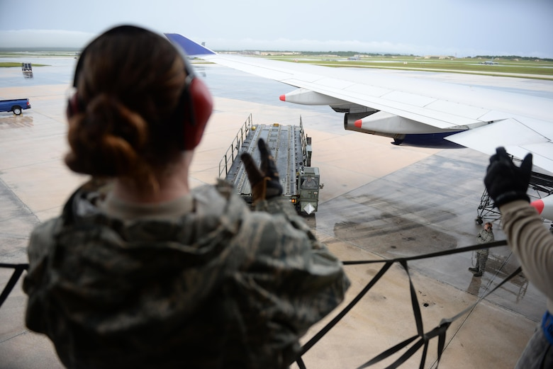 Senior Airman Hannah Stewart, 734th Air Mobility Squadron aircraft services technician, directs a Tunner 60K aircraft cargo loader as it approaches a Boeing 747 Sept. 7, 2016, at Andersen Air Force Base, Guam.The 734th AMS provides the capability to move cargo, personnel and equipment at a high velocity, ensuring Andersen AFB is prepared to meet mission requirements.(U.S. Air Force photo by Airman 1st Class Jacob Skovo)