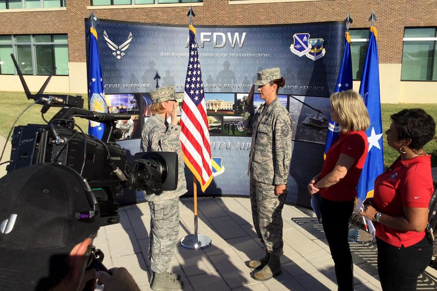 Col. Sharon Bannister, AFMS 79th Medical Wing commander, reenlists MSgt. Valerie Moore, 779th Medical Group first sergeant, during a live broadcast with Fox 5 DC at Joint Base Andrews on Sep. 23, 2016. AFDW hosted Fox5 DC for a live broadcast of FOX 5 News Morning and Good Day DC live from JBA in celebration of the Air Force's 69th Birthday. (U.S. Air Force photo/Tech. Sgt. Matt Davis)