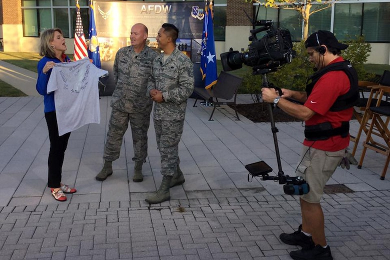 Fox 5 DC Anchor Holly Morris speaks with Lt. Col. Jon Goodman, 744th Communications Squadron commander, and Staff Sgt. Mario Marquez, 744th CS physical training leader, at Joint Base Andrews on Sep. 23, 2016. AFDW hosted Fox5 DC for a live broadcast of FOX 5 News Morning and Good Day DC live from JBA in celebration of the Air Force's 69th Birthday. (U.S. Air Force photo/Tech. Sgt. Matt Davis)