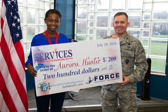 Col. Z. Walter Jackim, 45th Space Wing vice commander, (right), presents Aurora Hunter, with an award for placing second in the solo act preteen category for the 2016 Operations Talent Search at Patrick Air Force Base, Fla. Hunter was presented the award Sept. 21, 2106, during the Science, Technology, Engineering and Mathematics classroom opening and Worldwide Day of Play. (U.S. Air Force photo/Benjamin Thacker)