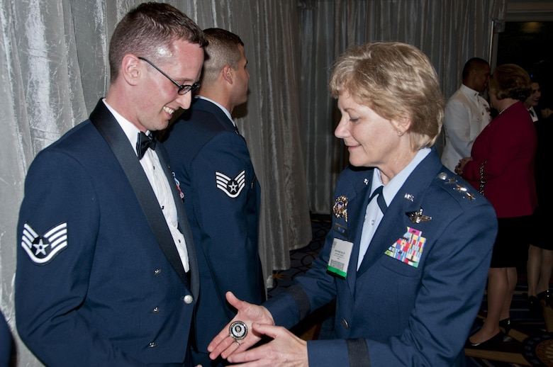 Lt. Gen. Maryanne Miller, chief of the Air Force Reserve and commander, Air Force Reserve Command, presents Staff Sgt. Aaron Tobler with a Chief of the Air Force Reserve coin during the Air Force Association banquet recognizing the Air Force's 12 Outstanding Airmen of the Year in Washington, D.C., Sept. 19, 2016. Tobler is a geospatial intelligence analyst with the 50th Intelligence Squadron, Beale Air Force Base, California.