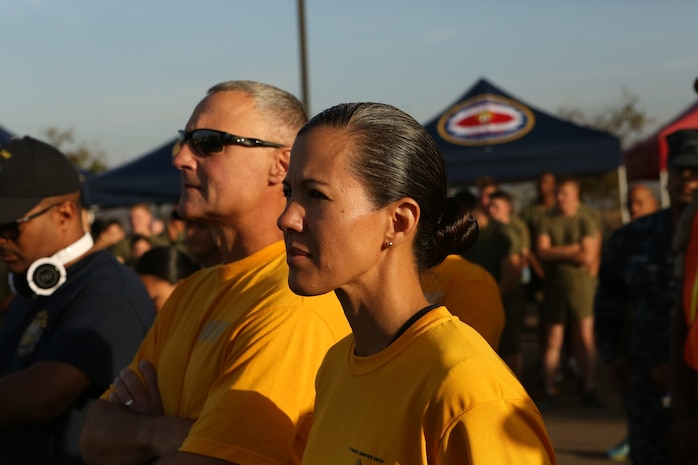 U.S. Navy Capt. Peter Ruocco and Master Chief Petty Officer Anna Wood listen to the guest speaker at the 2nd annual Suicide Prevention Awareness Walk aboard Camp Pendleton, Calif., Sept. 23, 2016. Ruocco is the commanding officer of 1st Dental Battalion, 1st Marine Logistics Group, and Wood is the unit's command master chief. The walk was held to increase awareness about suicide and highlight the resources available to help those in need. (U.S. Marine Corps photo by Lance Cpl. Joseph Sorci)