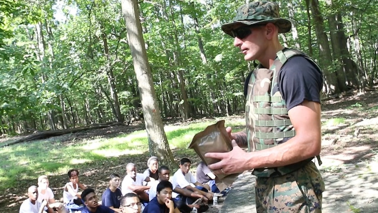 U.S. Marine Staff Sgt. Nicholas Safran teaches future Marines about the contents of a Meal-Ready-To-Eat at Sugarloaf Mountain in Urbana, Maryland, Aug. 20. Each future Marine had a bag that contained one MRE, two bottles of water, and one sports drink to get them through a 3.31-mile hike. Safran is the staff noncommissioned officer in charge of Recruiting Sub-station Rockville, Recruiting Station Frederick. (Official U.S. Marine Corps Photo by Sgt. Anthony J. Kirby/Released)