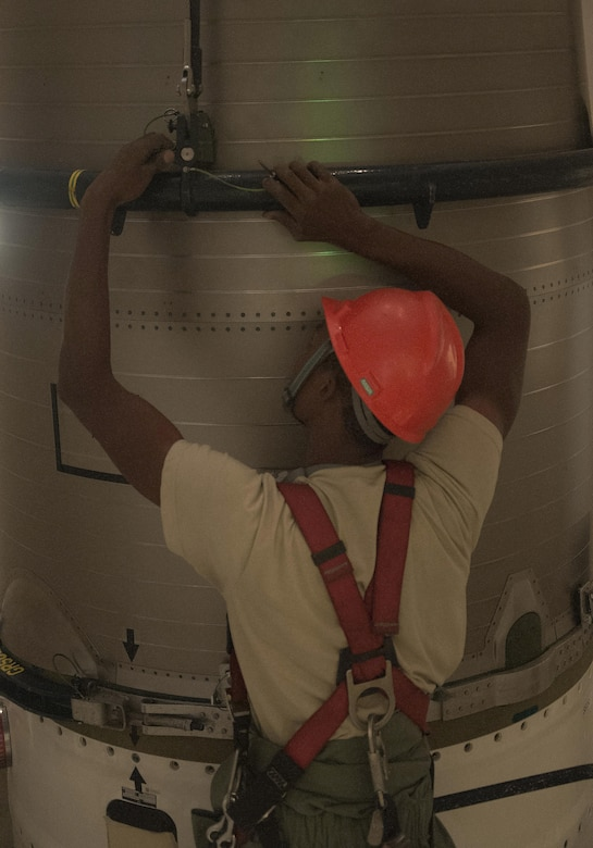 Airman 1st Class Jaylon Stanley, 90th Missile Maintenance Squadron maintainer, connects the reentry system handling fixture to the reentry system of a Minuteman III ICBM inside a launch facility in the F.E. Warren Air Force Base, Wyo., missile complex, Aug. 24, 2016. Once completely secured, the RS was hoisted into a payload transporter to allow maintainers to work on other portions of the ICBM. The 90th MMXS maintains 150 Minuteman III ICBMs and the associated LFs spread throughout three states and 9,600 square miles. (U.S. Air Force photo by Senior Airman)