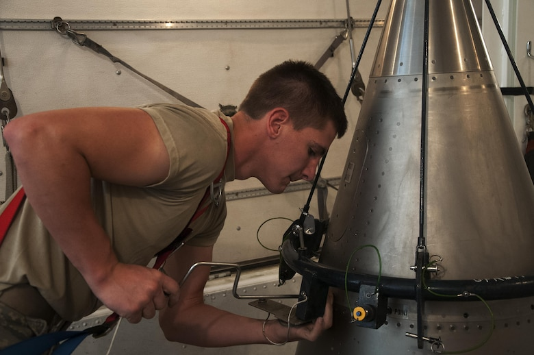 Airman 1st Class William Ray, 90th Missile Maintenance Squadron maintainer, removes the screws holding the nose point of a Minuteman III ICBM to the rest of the reentry system inside a payload transporter in the F.E. Warren Air Force Base, Wyo., missile complex, Aug. 24, 2016. The system was separated into two parts and secured inside a payload transporter. The 90th MMXS maintains 150 Minuteman III ICBMs and the associated LFs spread throughout three states and 9,600 square miles. (U.S. Air Force photo by Senior Airman Brandon Valle)