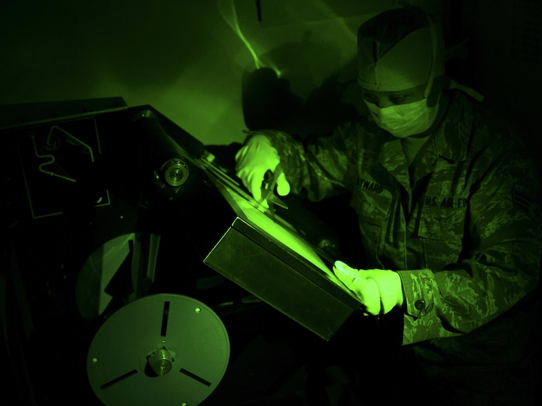 Senior Airman Heather Hayward, 9IS aerial film production specialist, cuts processed film during an Optical Bar Camera mission Feb. 17, 2015, at Beale Air Force Base, California. OBC Airmen work in a debris-free environment to develop 10,500 feet of film per mission, in either faint green light or complete darkness, using a Versamat 1140 film processor. From start to finish, it takes about nine hours to develop the entire film roll. (Air Force photo by Airman 1st Class Taylor A. Workman)