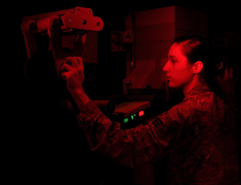 Senior Airman Shana Wojcik, 9IS quality assurance section lead, threads the original negative film through a Niagara printer in preparation for creating a duplicate positive copy Sept. 9, 2016, at Beale Air Force Base, California. The printing process is essential to the Optical Bar Camera mission because it is the only version of the film that geospatial analysts can exploit. In this section, it is safe to work under red or yellow light to prevent light damage to the duplicate film. (Air Force photo by Airman 1st Class Taylor A. Workman)