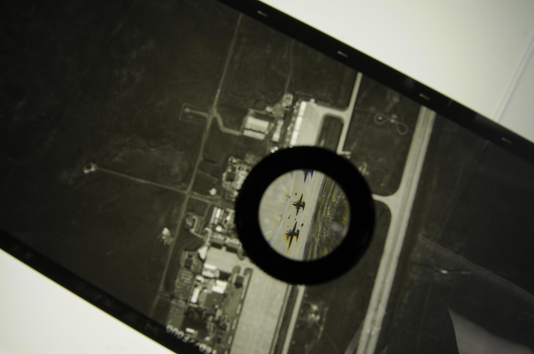 A section of Optical Bar Camera duplicate film is magnified using a loupe, showing two U-2 Dragon Lady aircraft on the Beale Air Force Base flightline. The OBC is carried by the U-2, which routinely flies at an altitude of more than 70,000 feet. (Air Force photo by Airman 1st Class Taylor A. Workman)