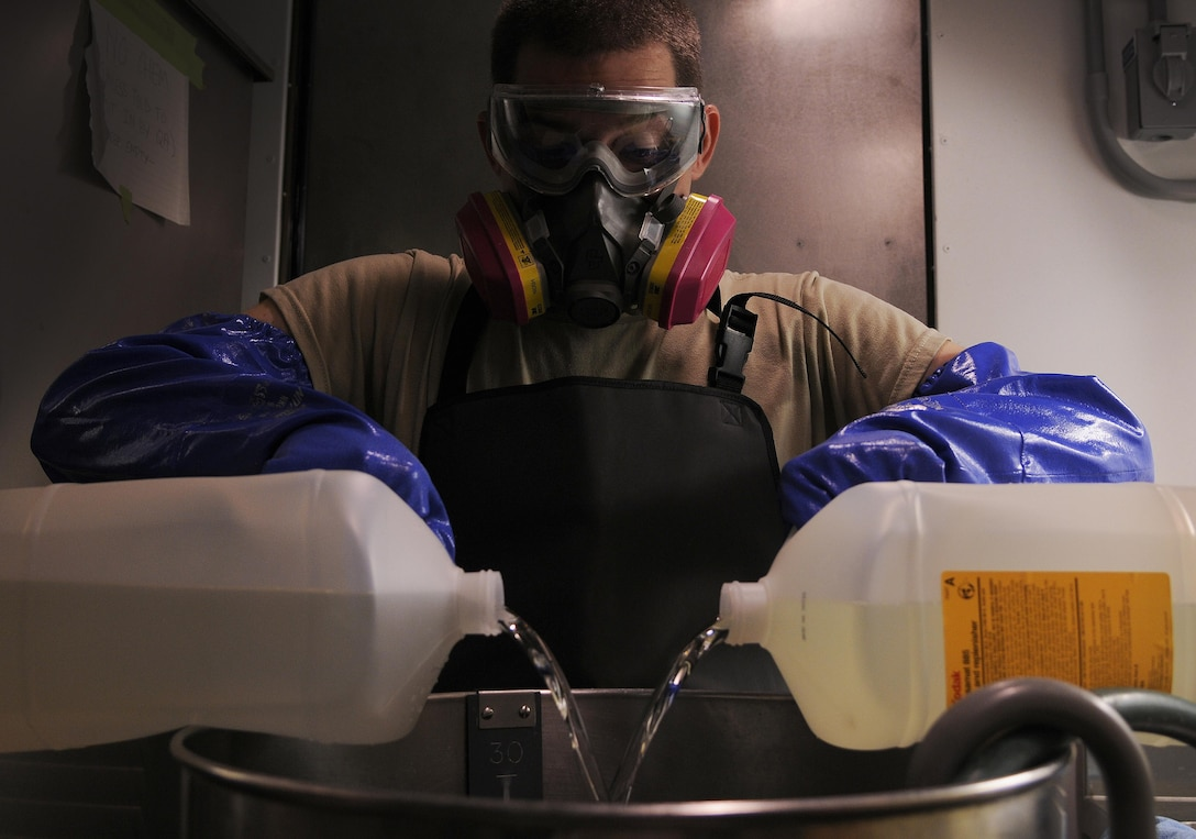 Staff Sgt. Christopher Hatch, 9IS aerial film processing section lead, pours fixer solution into a mixer Sept. 14, 2016, at Beale Air Force Base, California. Using the fixer and various other chemicals, film processors develop the wet-film imagery captured by the Optical Bar Camera. (Air Force photo by Airman 1st Class Taylor A. Workman)
