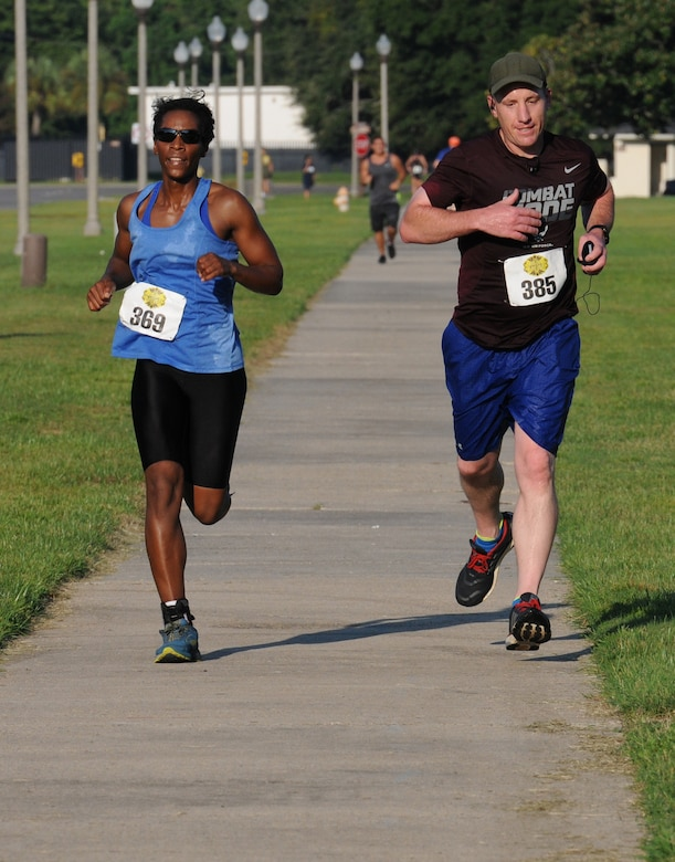Airman 1st Class Roslyn Lack, 338th Training Squadron student, and Lt. Col. Michael Zink, 338th TRS commander, run the last stretch of the 2-mile run, the final event of Keesler's mini-triathlon Sept. 23, 2016, on Keesler Air Force Base, Miss. The event also included a 200-yard swim and a 9-mile bike ride.