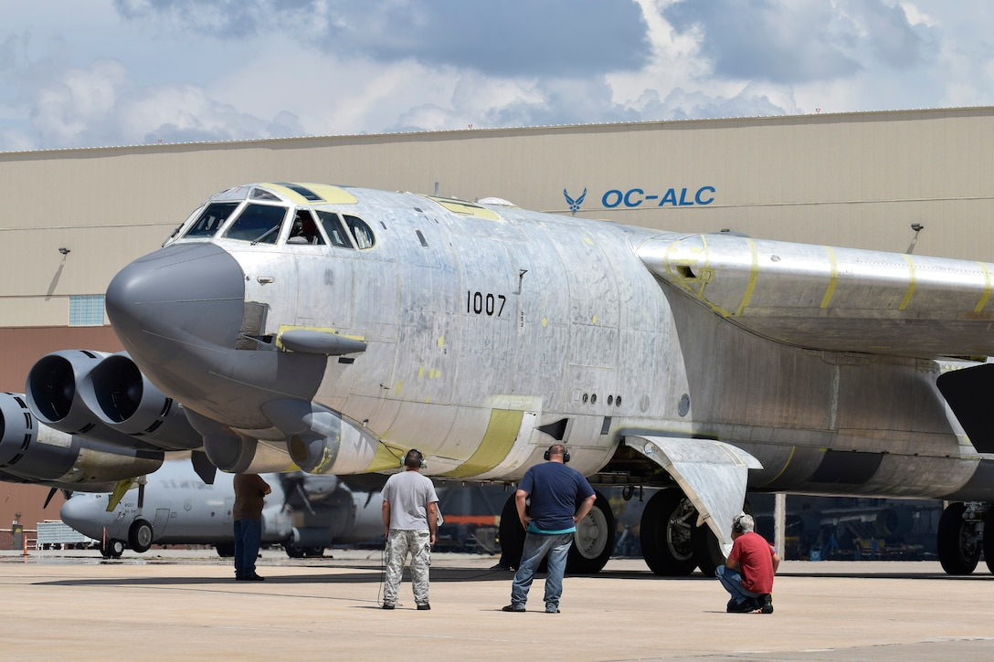 Maintenance personnel from the 565th Aircraft Maintenance Squadron work under and around B-52H 61-0007, 'Ghost Rider,' as the aircraft undergoes checks for an attempted functional test flight at the Oklahoma City Air Logistics Complex, Aug. 29, 2016, Tinker Air Force Base, Okla. 'OC-ALC' can be seen written on the hangar in the background as 'Ghost Rider' shines in natural metal as it completes a 19-month overhaul and upgrade to become the first B-52H to ever be regenerated from long-term storage with the 309th Aerospace Maintenance and Regeneration Group at Davis-Monthan AFB, Ariz., and returned to fully-operational flying status. (U.S. Air Force photo/Greg L. Davis)