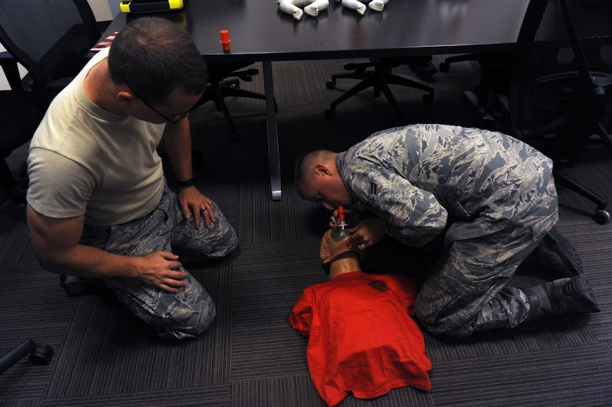 Senior Airman Timothy Wallace, 56th Medical Operation Squadron aerospace medical technician, observes Airman 1st Class Geoffrey Moreland, 56th Civil Engineer Squadron firefighter, performing cardiopulmonary resuscitation with a pocket CPR mask Sept. 20, 2016 at Luke Air force Base, Ariz. The pocket CPR mask contains a one way valve to prevent the spread of disease. (U.S. Air Force Photos by Airman 1st Class Pedro Mota)