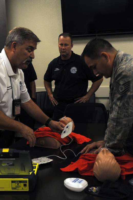 Steven Kinkade, 56th Civil Engineer Squadron assistant fire chief for training, and Tech Sgt. James Hickman, 56th CES fire fighter, demonstrate how to use an automated external defibrillator Sept. 20, 2016, at Luke Air Force Base, Ariz. Proper use of an AED is a core requirement for the CPR recertification class. (U.S. Air Force Photos by Airman 1st Class Pedro Mota)