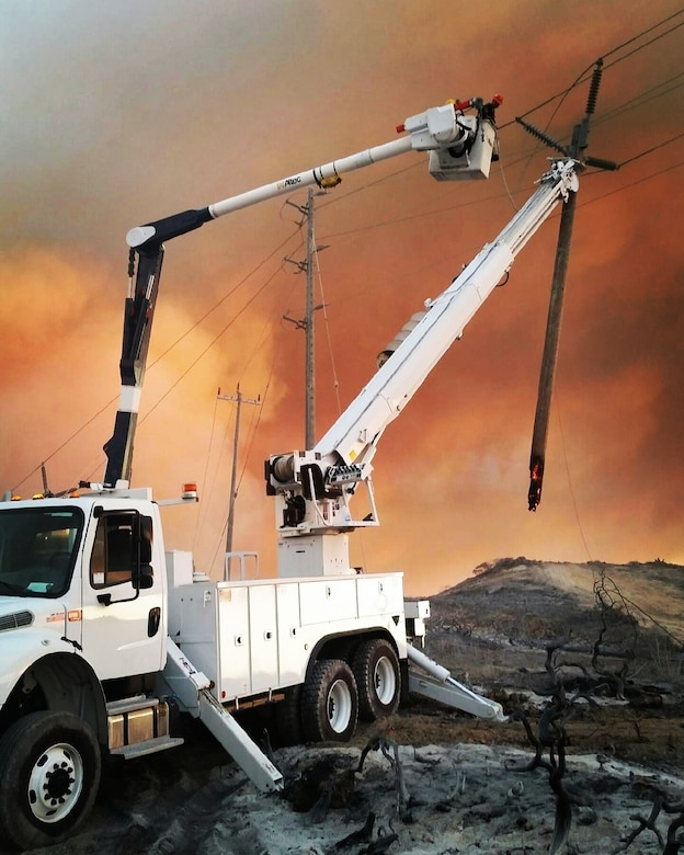 Electricians work to deengage power after a fire swept through portions of South Base, Sept. 19, 2016, Vandenberg Air Force Base, Calif. Vandenberg personnel, alongside community partners and a specialized incident management team, have worked to extinguish five separate wildland fires, here, since Sept. 17. (U.S. Air Force photo by Senior Airman Keith Martineau/Released)