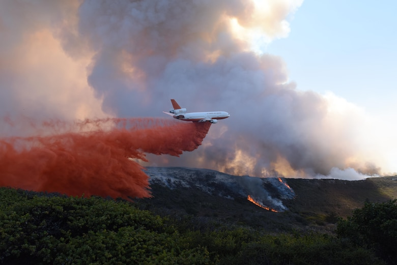 An aircraft drops fire retardant during a fire which swept through portions of South Base, Sept. 20, 2016, Vandenberg Air Force Base, Calif. Vandenberg personnel, alongside community partners and a specialized incident management team, have worked to extinguish five separate wildland fires, here, since Sept. 17. (U.S. Air Force photo by Staff Sgt. Shane Phipps/Released)