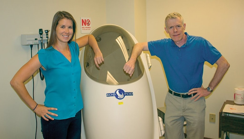 Kirsten David, Kirtland dietician, and Guy Leahy, Health Promotion Program coordinator, stand with the BodPod, a device that measures body fat percentage. They have a variety of services available to Airmen who want help meeting health and fitness goals. (Photo by Bud Cordova)