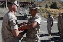 Lance Cpl. Javier Verdin Jr, supply administration specialist, receives his meritorious promotion warrant from Capt. Edwin Powers, Headquarters Company Commander, after being meritoriously promoted to lance corporal at the Marine Corps Mountain Warfare Training Center, Sept 2, 2016.  The meritorious board consisted of a run up Mountain Leader's Loop, a functional fitness competition, and a question-and-answer session with a panel of staff non-commissioned officers