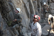 "SSgt.  Jonathon Campos, a ""red hat"" instructor, studies a climbing lane with a student during Assault Climbers Course 3-16 at Marine Corps Mountain Warfare Training Center, Sept 8, 2016.  Instructors at MCMWTC undergo rigorous training to be qualified to teach mountain warfare tactics, techniques and procedures."