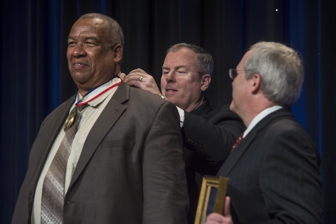Deputy Defense Secretary Bob Work, center, presents the Spirit of Hope Award to Timothy Bryant, commander of Veterans of Foreign Wars Post 3000, at the Pentagon, Sept. 28, 2016. Six individuals and one organization received the award, named after Bob Hope. DoD photo by Navy Petty Officer 1st Class Tim D. Godbee
