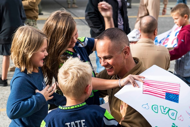 Navy Senior Chief Petty Officer Chad Sweetser hugs his children after returning home to Naval Air Station Whidbey Island, Wash., Sept. 23, 2016. Sweetser is assigned to Patrol Squadron 40, which conducted operations in the 5th and 7th Fleet areas of responsibility. Navy photo by Petty Officer 3rd Class Caleb Cooper