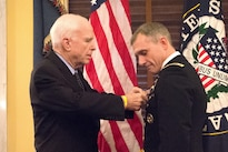 U.S. Sen. John McCain of Arizona pins a Soldier's Medal on Army Lt. Col. David P. Diamond during a ceremony on Capitol Hill, Sept. 27, 2016. Diamond received the medal for helping to save lives following the bombings at the Boston Marathon three years ago. Army photo by John Martinez