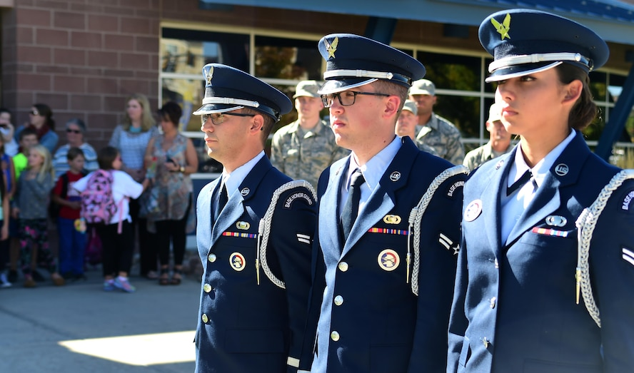 From the left: Airman 1st Class Paul Lombardi, Airman 1st Class Nathan Doty and Airman 1st Class Feather Yahola, U.S. Air Force Mile High Honor Guard members, stand at attention prior to lowering the American flag Sep. 27, 2016, at Aurora Frontier P-8 in Aurora, Colo. Members of the honor guard volunteered to put on a demonstration for elementary students to educate them on properly lowering and folding the flag. (U.S. Air Force photo by Airman Holden S. Faul/ Released)