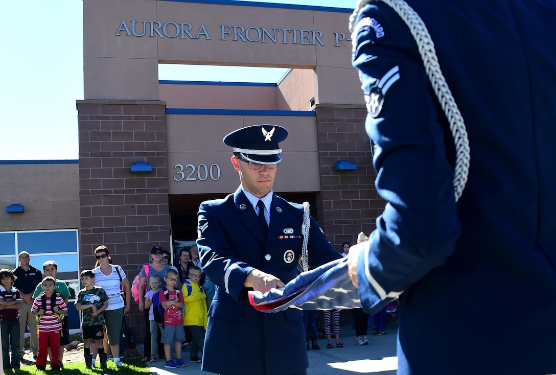 Airman 1st Class Paul Lombardi, U.S. Air Force Mile High Honor Guard member, folds the American flag during a demonstration Sep. 27, 2016, at Aurora Frontier P-8 in Aurora, Colo. Members of the honor guard volunteered to put on a demonstration for elementary students to educate them on properly lowering and folding the flag. (U.S. Air Force photo by Airman Holden S. Faul/ Released)