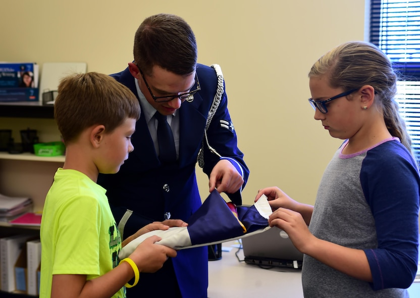 Airman 1st Class Nathan Doty, U.S. Air Force Mile High Honor Guard member, teaches students how to strategically tuck in the excess material of the flag after properly folding it Sep. 27, 2016, at Aurora Frontier P-8 in Aurora, Colo.  Since students at Aurora Frontier P-8 raise and lower the flag each day, faculty and staff invited the Mile High Honor Guard to teach the students proper flag etiquette. (U.S. Air Force photo by Airman Holden S. Faul/ Released)
