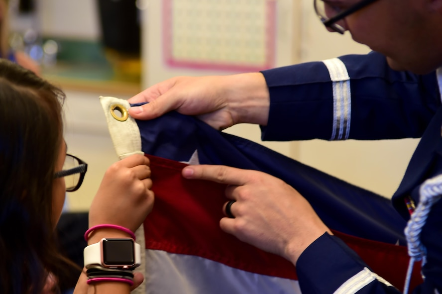 Airman 1st Class Paul Lombardi, U.S. Air Force Mile High Honor Guard member, teaches a student how to properly fold the American flag Sep. 27, 2016, at Aurora Frontier P-8 in Aurora, Colo. Folding the American flag correctly is a precise job, and one that has become part of military tradition. (U.S. Air Force photo by Airman Holden S. Faul/ Released)