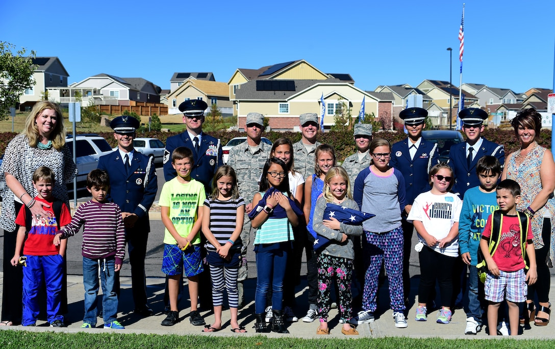 U.S. Air Force Mile High Honor Guard members stand with students and faculty after demonstrating and teaching them how to properly lower and fold the American flag Sep. 27, 2016, at Aurora Frontier P-8 in Aurora, Colo. Members of the honor guard volunteered to put on a demonstration for elementary students to educate them on proper flag etiquette. (U.S. Air Force photo by Airman Holden S. Faul/ Released)