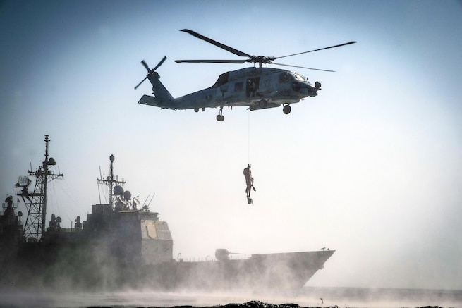 An MH-60R Seahawk helicopter hoists two sailors during search and rescue training in front of the USS Monterey in the Persian Gulf, Sept. 23, 2016. The Monterey is supporting maritime security operations efforts in the U.S. 5th Fleet area of operations. Navy photo by Petty Officer 2nd Class William Jenkins