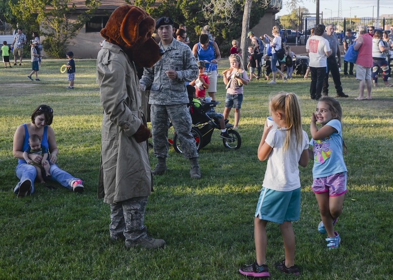 A security forces member wearing a McGruff the Crime Dog costume greets two children during the annual Zoo After Hours event at Alameda Park Zoo in Alamogordo, N.M. on Sept. 24, 2016. McGruff the Crime Dog is a cartoon bloodhound that helps to raise crime awareness among children. (U.S. Air Force photo by Airman 1st Class Alexis P. Docherty)