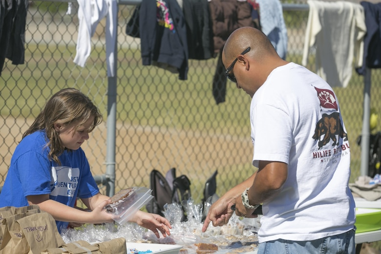 Lacy Tavzel , member, American Red Cross Youth Group, sells baked goods to a Combat Center patron during their Yard and Bake Sale at the Lincoln Military Housing Athletic Field aboard Marine Corps Air Ground Combat Center Twentynine Palms, Calif., Sept. 17, 2016. The event was used as a fund raiser for the youth group and charities. (Official Marine Corps photo by Cpl. Thomas Mudd/Released)
