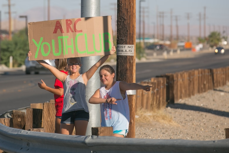 The American Red Cross Youth Group advertises a yard and bake sale by Del Valle Road aboard Marine Corps Air Ground Combat Center Twentynine Palms, Calif., Sept. 17, 2016. The event was used as a fund raiser for the youth group and charities. (Official Marine Corps photo by Cpl. Thomas Mudd/Released)