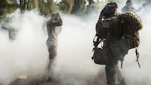 Marines don their gas masks as simulated hostiles use O-chlorobenzalmalononitrile gas during a raid as part of a training exercise aboard the Kahuku Training Facility, Sept. 20, 2016. The exercise is part of a 7-week-long training known as the Advance Infantry Course. The Advance Infantry Course, which is conducted by the Advance Infantry Battalion, Detachment Hawaii, is an advanced 0311 rifleman Military Occupational Specialty course for squad leaders who are currently serving in the operating field.