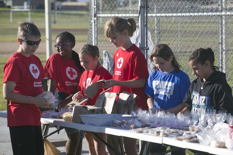 The American Red Cross Youth Group organizes baked goods during a yard and bake sale at the Lincoln Military Housing Athletic Field aboard Marine Corps Air Ground Combat Center Twentynine Palms, Calif., Sept. 17, 2016. The event was used as a fund raiser for the youth group and charities. (Official Marine Corps photo by Cpl. Thomas Mudd/Released)