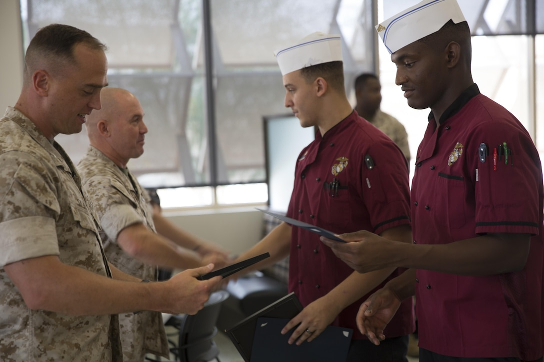 Lance Cpl. Kenneth Martin and Cpl. Darius Henson, food service specialists, Headquarters Battalion, receive certificates after winning people's choice and chef's choice during the Chef of the Quarter competition at Phelps Mess Hall aboard Marine Corps Air Ground Combat Center, Twentynine Palms, Calif., Sept. 21, 2016. The competition is held every quarter and provides Marine and civilian chefs aboard the installation an opportunity to showcase their cooking expertise. (Official Marine Corps photo by Cpl. Medina Ayala-Lo/Released)