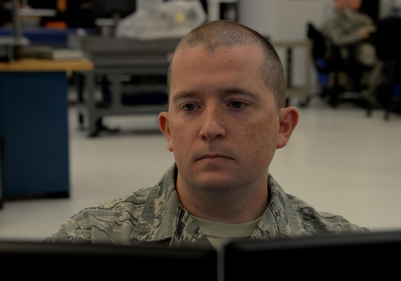 Staff Sgt. Timothy Gould, 60th Maintenance Squadron precision measurement equipment laboratory technician from Buffalo, New York, reviews a report on his computer at Travis Air Force Base, Calif., Sept. 27, 2016. The Travis PMEL team conducts about 12,000 calibrations a year and supports units at 15 bases. (U.S. Air Force photo/Tech. Sgt. James Hodgman)