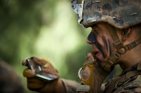 U.S. Marine Corps Lance Cpl. Anthony Acedo, rifleman with 1st Battalion, 7th Marine Regiment, applies cammie paint during the Advanced Infantry Course at Kahuku Training Area, Sept. 20, 2016. AIC is intermediate training designed to enhance and test the Marine's skills and leadership abilities as squad leaders in a rifle platoon.