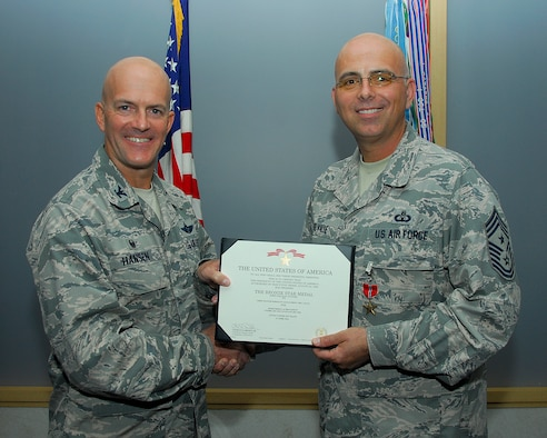 U.S. Air Force Col. Andrew Hansen, 51st Fighter Wing commander, and Chief Master Sgt. Alexander Del Valle, 51st FW command chief, pose for a photo after Del Valle received a Bronze Star Medal Sept. 27, 2016, at Osan Air Base, Republic of Korea. Del Valle received the BSM for his accomplishments serving as the 438th Air Expeditionary Wing command chief at Forward Operating Base Oqab, Kabul, Afghanistan, from February 2015 to January 2016. (U.S. Air Force photo by Kyong Hwan Song)