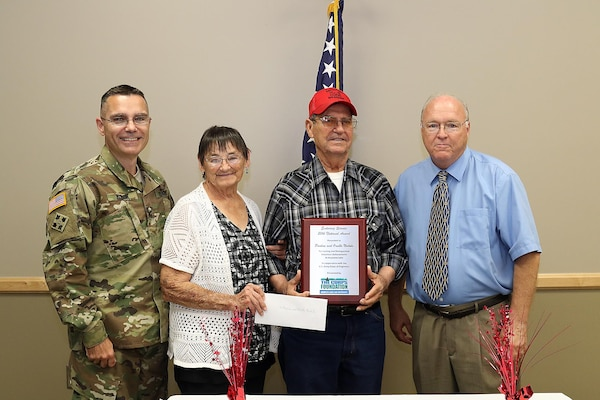"Col. Christopher Hussin, Commander, Tulsa District, U.S. Army Corps of Engineers joins Greg Miller, Chairperson Board of Directors, The Corps Foundation, in presenting Orville and Pauline Nichols with the ""Volunteer Enduring Service Award,"" Sept. 22, at the Case Community Center, Sand Springs, Okla.  The Nichols received the national award for their contribution of over 26,000 hours of volunteer work to Keystone Lake."