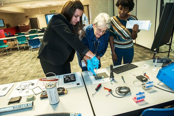Meghan Kipp (left), Applied DNA Sciences' technical product manager Government and Military Programs, demonstrates current DNA marking technology to DLA Land and Maritime associates during their research and development update visit.