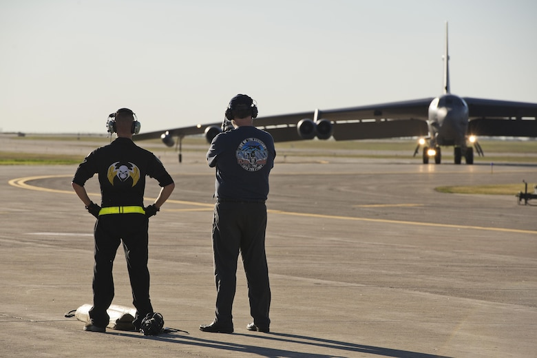 Staff Sgt. Dylan Wall, 5th Aircraft Maintenance Squadron dedicated crew chief (left), and Robert Crane, 5th Logistics Readiness Squadron vehicle management flight chief, watch as the B-52H Stratofortress Ghost Rider taxis to the alternate parking area at Minot Air Force Base, N.D., Sept. 27, 2016. Crane was the primary crew chief on Ghost Rider when it was stationed here in the 90s. (U.S. Air Force photo/Airman 1st Class J.T. Armstrong)
